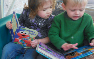 Two toddlers reading