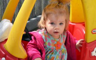 girl playing in toddler car