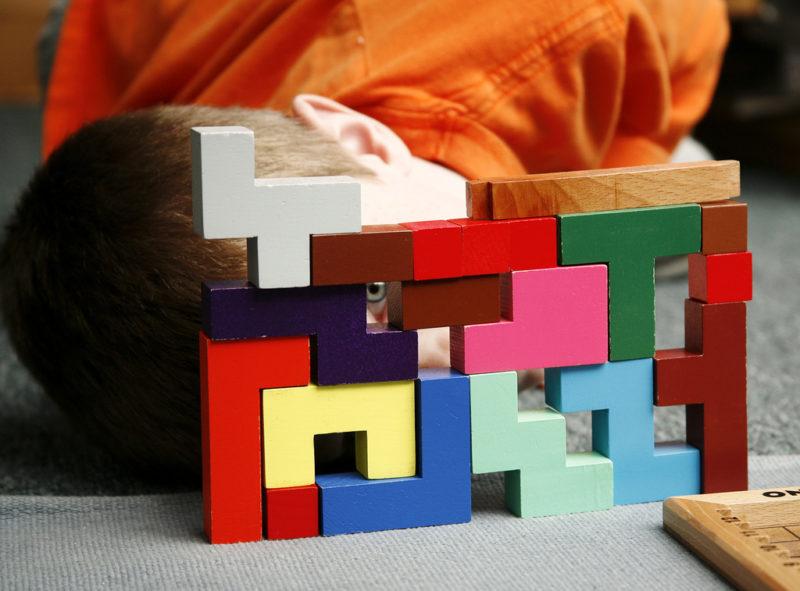 boy looking through montessori blocks colorful creative success