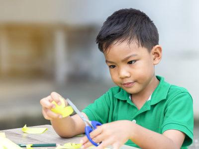boy focusing on cutting skills