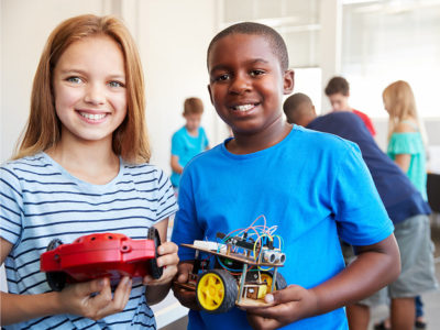 two students showing a robot project together